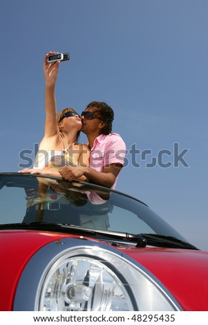 Couple in red convertible car taking picture - stock photo