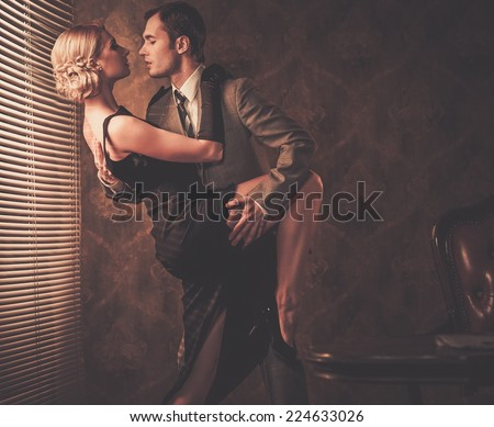 Couple in retro interior near a window - stock photo