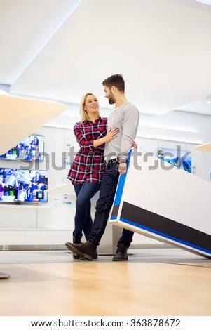 Couple in shopping at TV store. They are walking and holding big unpacked tv. Shallow depth of field. - stock photo