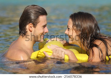 Couple in summer vacation bathing in the water of the beach and looking each other - stock photo
