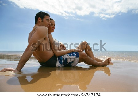 Couple in swimsuit laid on the sand face to the sea - stock photo