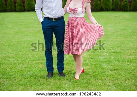 Couple in the grass, only legs, engagement photo, before wedding, picnic, sunny day, romantic photo, without face, girl with pin up dress, vintage color - stock photo