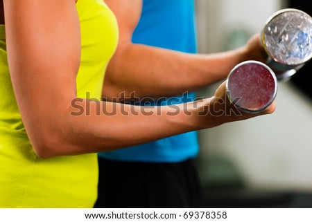 couple in the gym, rivaling each other, exercising with dumbbells - stock photo