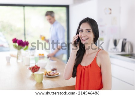 couple in the kitchen at the morning woman at phone at foreground