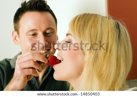 Couple in the kitchen: he  is feeding her strawberries - stock photo