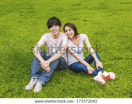 couple in the park sitting on the grass embracing each other - stock photo