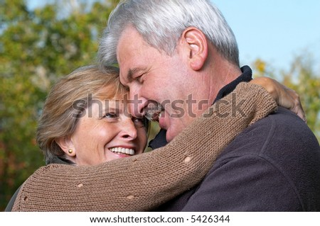 Couple in their fifties hugging each other. - stock photo