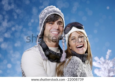 couple in their late 20s in ski hats and glasses - stock photo