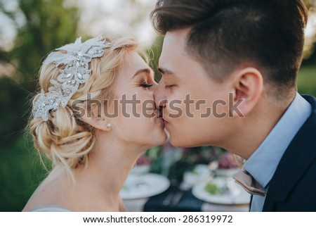 Couple in their wedding clothes kissing in a garden on a background decorated table, the bride and groom