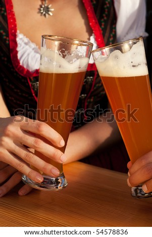 Couple in traditional Bavarian Tracht - Dirndl and Lederhosen - in a beer tent at the Oktoberfest or in a beer garden clinking glasses with whet beer, only glasses and torsos to be seen - stock photo