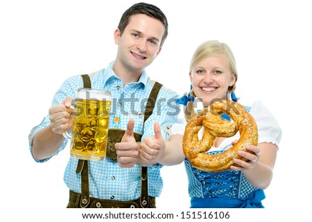 Couple in traditional bavarian tracht holding Oktoberfest beer steins and pretzel - stock photo