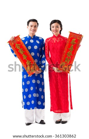 Couple in traditional Vietnamese dresses showing New Year scrolls - stock photo