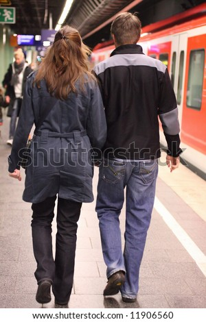 couple in underground station - incoming train