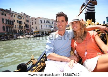 Couple in Venice having a Gondola ride on canal grande - stock photo