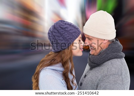 Couple in warm clothing facing each other against blurry new york street