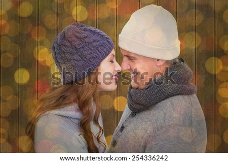 Couple in warm clothing facing each other against close up of christmas lights - stock photo