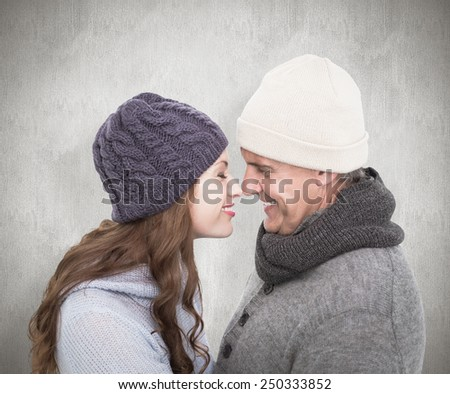 Couple in warm clothing facing each other against white background - stock photo