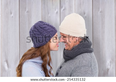 Couple in warm clothing facing each other against wooden background - stock photo