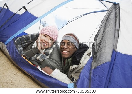 Couple in warm clothing, lying down in tent - stock photo