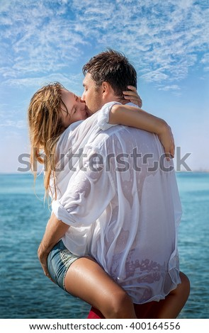 couple in wet clothes kissing in the sea on the beach - stock photo
