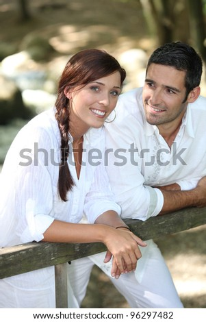 Couple in white leaning on a wooden fence - stock photo