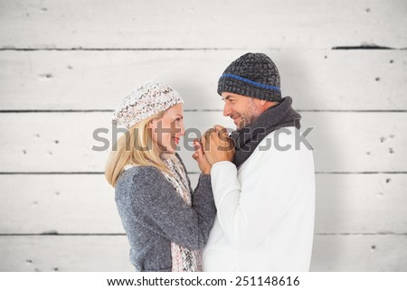Couple in winter fashion embracing against white wood - stock photo