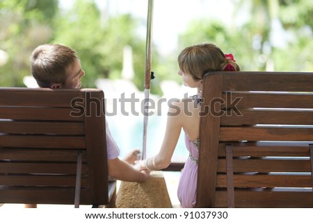 couple in wooden chaise longues near swimming pool - stock photo