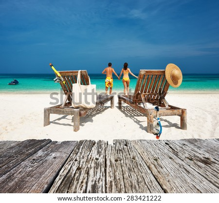 Couple in yellow relax on a tropical beach at Maldives - stock photo