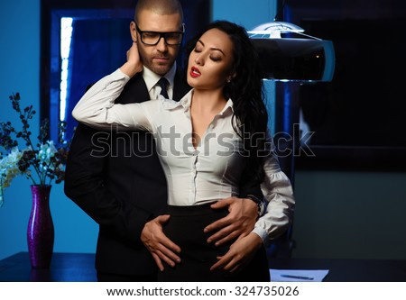 Couple indoors. Sensual brunette and handsome businessman. Office romance concept - stock photo