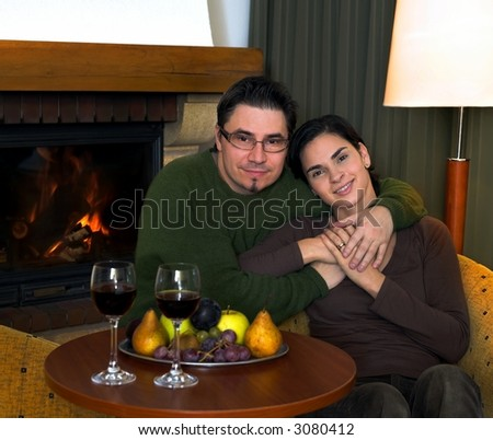 Couple is relaxing at home by the fireplace. - stock photo