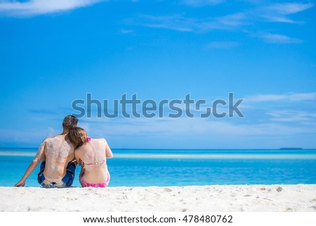 Couple is sitting on the shore of tropical island.