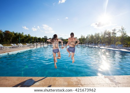 Couple jumping into pool. Summer vacations - stock photo