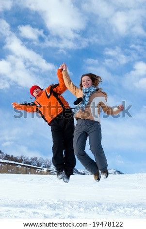 Couple jumping over blue sky in winter mountains Tien Shan - stock photo