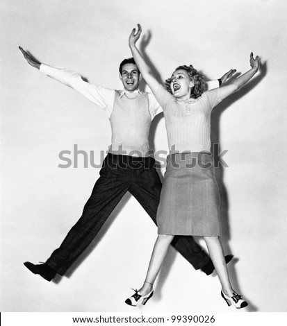 Couple jumping with their arms outstretched - stock photo