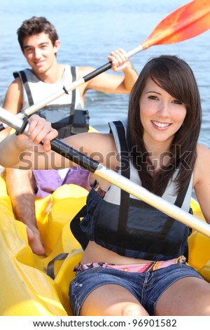 Couple kayaking on a warm summer's day - stock photo