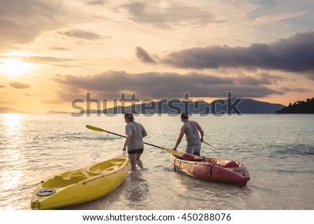 Couple kayaking on the beach in sunset at tropical - stock photo