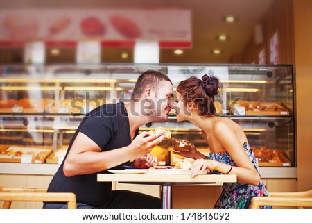 couple kissing and eating cakes in cafe - stock photo