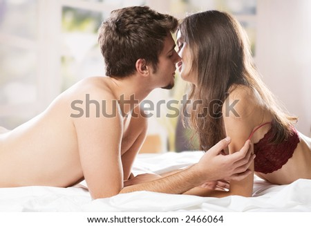 Couple kissing and hugging on bed in bedroom, in passion - stock photo