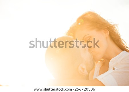 Couple kissing at sunset - photographed against sun - stock photo