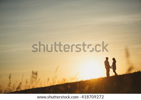 Couple kissing at sunset. silhouette of a loving couple at sunset in a wheat field. - stock photo