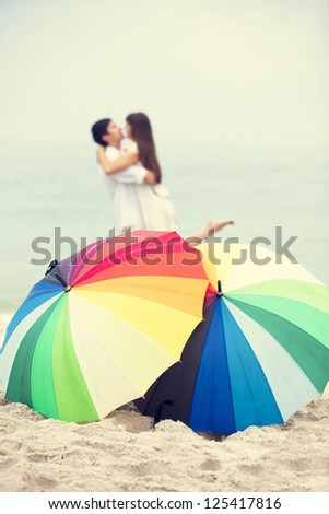 Couple kissing at the beach with umbrella - stock photo