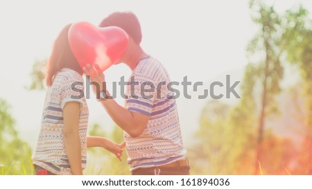 Couple kissing behind a red heart balloons with Sunlight - stock photo