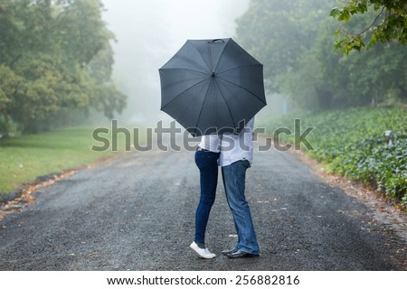 couple kissing behind the umbrella in the mist - stock photo