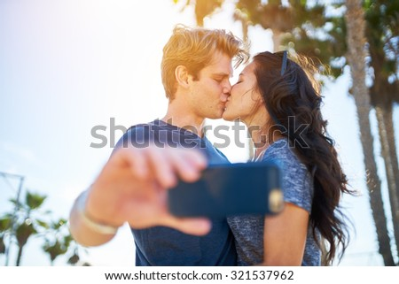 couple kissing for romantic selfie in front of sun and palm trees with lens flare and selective focus - stock photo