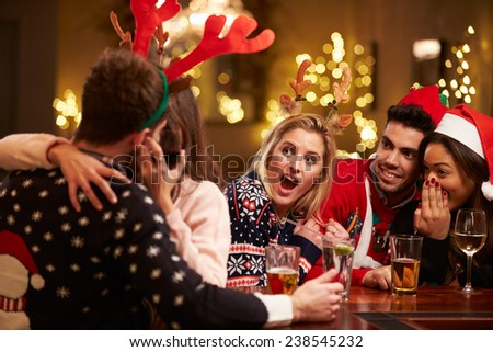 Couple Kissing In Bar As Friends Enjoy Christmas Drinks - stock photo