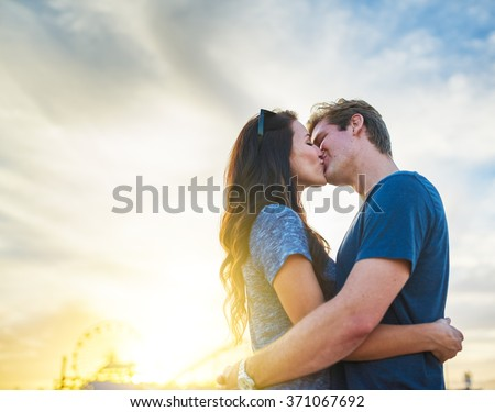 couple kissing in front of santa monica california at sunset - stock photo