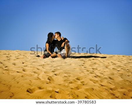 Couple kissing in the dunes of Fuerteventura, Spain - stock photo
