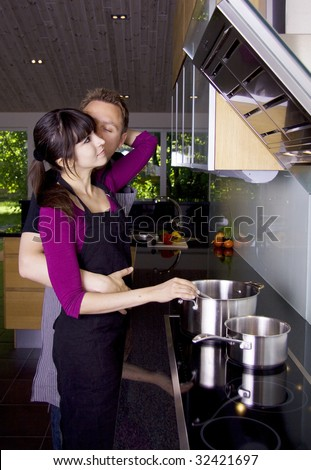 Couple kissing in the kitchen while cooking