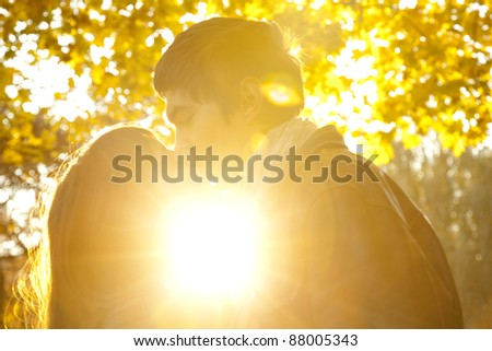 Couple kissing in the park at sunset. - stock photo