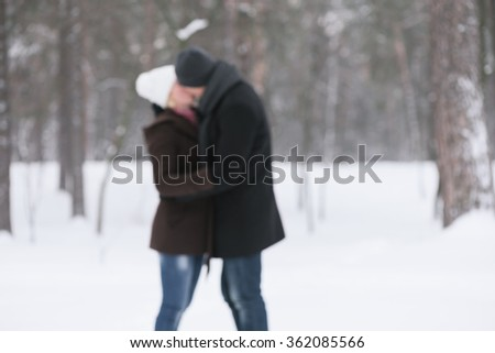 Couple kissing in winter park. Romantic date. Photo in defocusing - stock photo